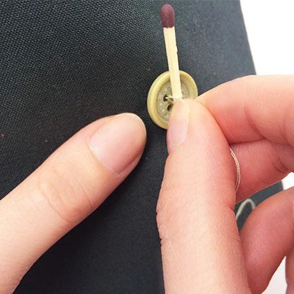 Der Gegenknopf wird mithilfe eines Streichholzes angenäht.