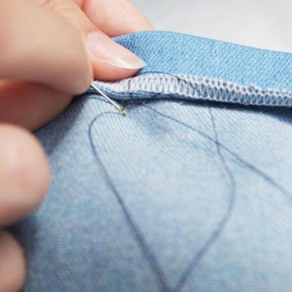 Der umgeschlagene Saum wird mit Nadel und Faden per Hand festgenäht.