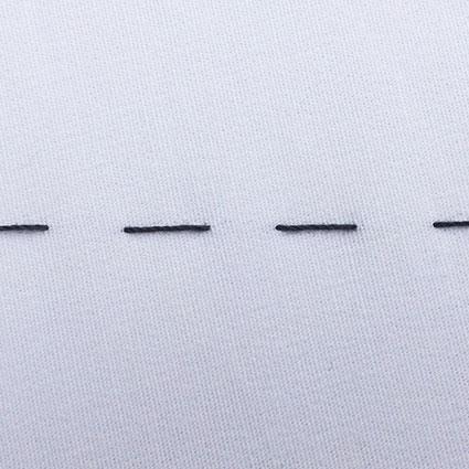 Man sieht einzelne kurze Heftstiche auf Stoff.