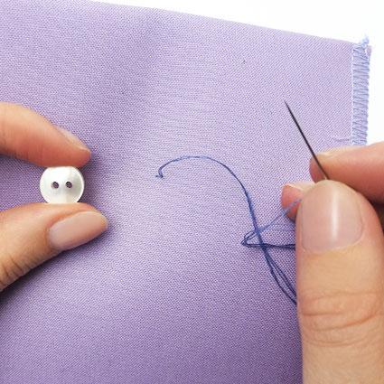 Der Knopf wird mit Nadel und Faden auf den Stoff genäht.