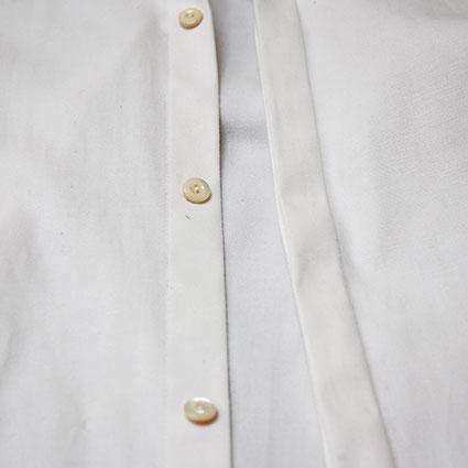 Eine offene Knopfleiste eines Hemdes ist zu sehen.