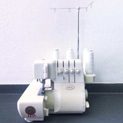 Eine weiße Overlockmaschine mit vier Garnrollen ist abgebildet.