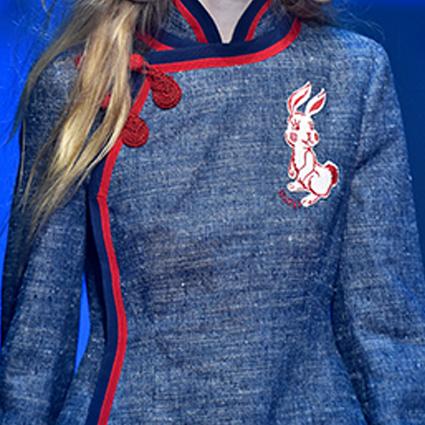 Ein roter Posamentenverschluss ist an der Jacke angebracht.