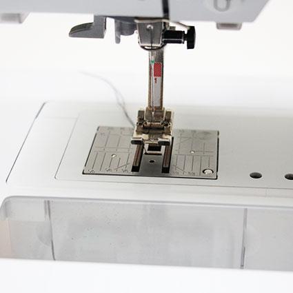 Der Bereich des Nähfußes und Stichplatte an einer Nähmaschine ist abgebildet. Er zeigt den Transportbereich.